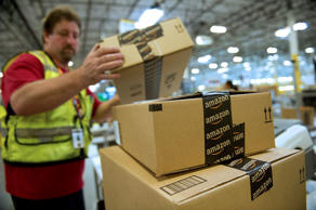 An employee stacks boxes filled with merchandise for shipment at the Amazon.com ...