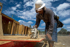 A contractor cuts wood while working at the PulteGroup Inc. Sage housing develop...