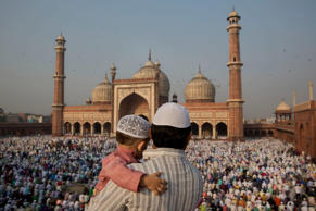 A man carries a child as they gather to offer prayers at Jama Masjid mosque in New Delhi on October 6, 2014. Muslims around the world celebrate Eid al-Adha, or the Feast of the Sacrifice, to commemorate the prophet Abraham's offering for his son to god.