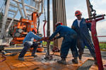 Floor hands Jose Garza, left, Jose Salinas, center, and Omar Cano make a pipe connection on Orion Drilling Co.'s Perseus drilling rig near Encinal in Webb County, Texas, U.S., on Monday, March 26, 2012. The Perseus is drilling for oil and gas in the Eagle Ford Shale, a sedimentary rock formation underlying an area of South and East Texas.