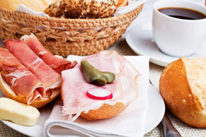 Traditional german breakfast - a roll with butter and ham on a plate, decorated with gherkin and radish