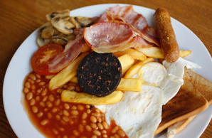 A traditional full English breakfast of sausages, chips, baked beans, bacon, bla...