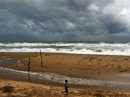 "An Indian boy plays on the beach as waves break on the Bay of Bengal coast near Gopalpur, in Ganjam district, 140 kilometers (87 miles) south of Bhubaneswar, India, Saturday, Oct. 11, 2014. The India Meteorological Department described Cyclone Hudhud as a ""very severe"" storm that could pack winds of 195 kilometers (120 miles) per hour and cause torrential rains when it makes landfall near the port city of Visakhapatnam around noon Sunday."