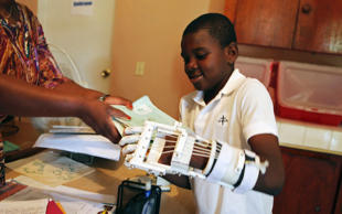 Handicapped Haitian boy Stevenson Joseph learns to use a 3D-printed prosthetic hand at an orphanage.