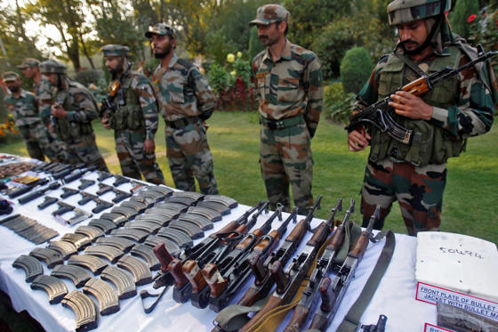 Indian army soldiers display arms and ammunition captured from militants