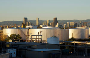 Oil storage tanks are seen at sunrise with the Rocky Mountains and the Denver downtown skyline in the background October 14, 2014. Brent crude fell almost 3 percent to a fresh low near $86 a barrel on Tuesday, trading at its weakest level since 2010 after the West's energy watchdog cut its estimates for oil demand this year and next.