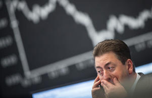 A stock trader works at the stock exchange in Frankfurt am Main on October 16, 2014. German stocks plunged more than 2.0 percent in late morning trade on the Frankfurt stock exchange, giving up earlier gains as doubts grow about global recovery, traders said. The blue-chip DAX 30 index plummeted 2.53 percent to an intraday low of 8,354.97 points, adding to already heavy losses the day before. The mid-cap MDAX index was also showing a loss of around 2.0 percent at 14,458.46 points.