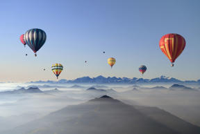 Five colorful hot air balloons flying over layers of mountain ridges partly covered in mist. Morning, sun, Austrian Alps, Groß Glockner, Tyrolia, blue sky.Taken in fall 2011.