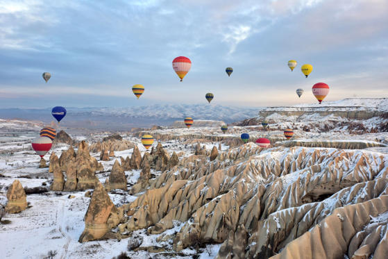 Slide 1 of 27: NEVSEHIR, TURKEY - DECEMBER 23:  Hot air balloons fly over Cappadocia, a historical region in Central Anatolia, largely in Nevsehir Province, known for the fairy chimneys, during the winter season, on December 23, 2014.  (Photo by Murat Oner Tas/Anadolu