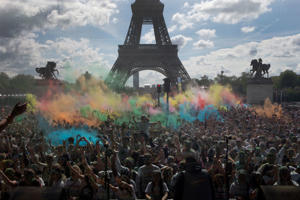 People take part in the Color Run near the Eiffel Tower, in Paris, Sunday, April 16, 2017. The Color Run is a 5 kilometer (3.1 mile) running event where participants are covered in bright colored powder at each check station and is less about speed and m