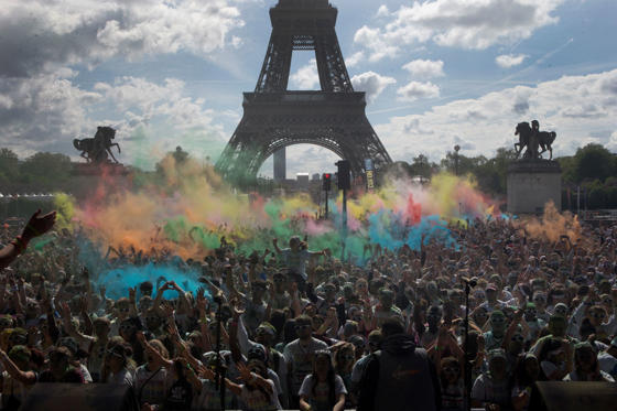 Slide 1 of 30: People take part in the Color Run near the Eiffel Tower, in Paris, Sunday, April 16, 2017. The Color Run is a 5 kilometer (3.1 mile) running event where participants are covered in bright colored powder at each check station and is less about speed and m