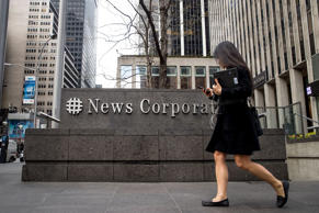 A woman walks past the News Corp. and Fox News headquarters in Midtown Manhattan...
