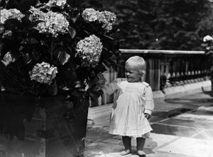 July 1922: At one year old, Prince Philip of Greece shows an interest in things floral.