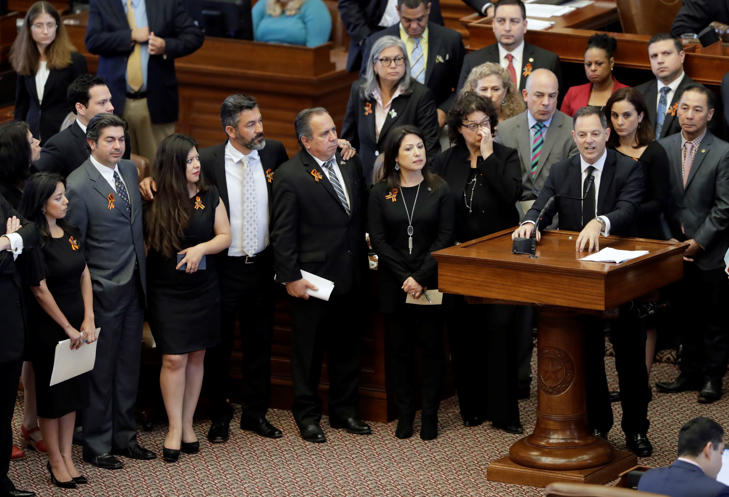 "Texas Rep. Rafael Anchia, D-Dallas, at podium, is surrounded by fellow lawmakers as he speaks against an anti-""sanctuary cities"" bill that has already cleared the Texas Senate and seeks to jail sheriffs and other officials who refuse to help enforce federal immigration law, Wednesday, April 26, 2017, in Austin, Texas."