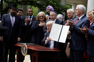 President Donald Trump holds a signed executive order aimed at easing an IRS rule limiting political activity for churches, Thursday, May 4, 2017, in the Rose Garden of the White House in Washington.