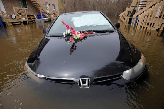 Slide 1 of 19: An abandoned car with a sign reading 'R.I.P.' in the windshield is seen in a flooded residential area in Gatineau, Que., May 8, 2017.