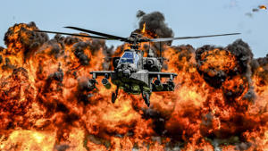 An AH-64D Apache attack helicopter flies in front of a wall of fire during the South Carolina National Guard Air and Ground Expo at McEntire Joint National Guard Base, South Carolina, U.S. on May 6, 2017.