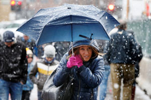 A woman walks with an umbrella as snow falls in Boston, Saturday, April 1, 2017.