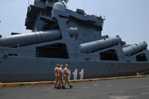 Russian sailors of the missile-guided cruiser Varyag walk past their ship showing the P-500 Bazalt long range anti-ship missile sytem during a shipboard tour in Manila on April 22, 2017.