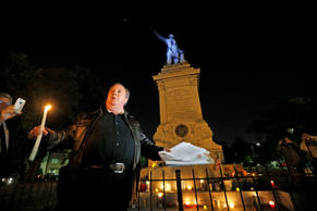 Charles Lincoln speaks during a candlelight vigil at the statue of Jefferson Dav...