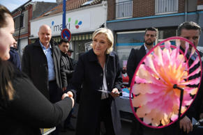 French presidential election candidate for the far-right Front National (FN) party Marine Le Pen (C), escorted by her bodyguard Thierry Legier (L) tours the marketplace in Rouvroy near Henin-Beaumont, northern France.