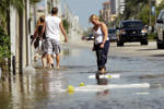 Local resident Jessica Deal makes her way through floodwater caused by a seasonal king tide, Monday, Oct. 17, 2016, in Hollywood, Fla.