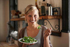 A woman eats a salad in her kitchen (Photo: Getty).