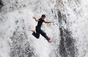 A man jumps off the cliff of Serendah waterfall in Rawang, outside Kuala Lumpur, Malaysia, Monday, April 24, 2017. Serendah is a small town located 60 kilometers (37 miles) from the city center. (AP Photo/Daniel Chan)