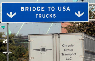 A commercial automotive supplier truck passes under a sign leading to the Ambassador bridge crossing over to Detroit, Michigan from Windsor, Ontario September 28, 2013.