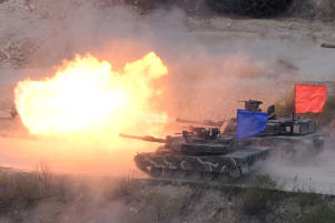 A South Korean K1A2 tank (blue) and a US M1A2 tank (red) fire live rounds during a joint live firing drill between South Korea and the US at the Seungjin Fire Training Field in Pocheon, 65 kms northeast of Seoul, on April 26, 2017.