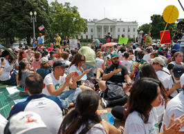 Demonstrators sit on the ground along Pennsylvania Ave. in front of the White House in Washington, Saturday, April 29, 2017, during a demonstration and march. Thousands of people gathered across the country to march in protest of President Donald Trump's environmental policies, which have included rolling back restrictions on mining, oil drilling and greenhouse gas emissions at coal-fired power plants. The demonstrators sat down for 100 seconds to mark President Trump's first 100 days in office.
