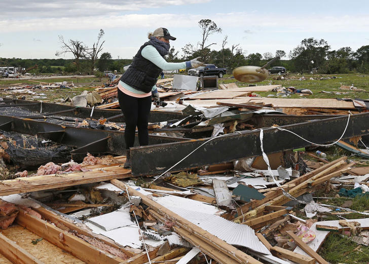 A woman tosses a frying pan out of the rubble, April 30, 2017, while sifting through the remains of a trailer home destroyed when a large tornado hit the area near Canton, Texas.