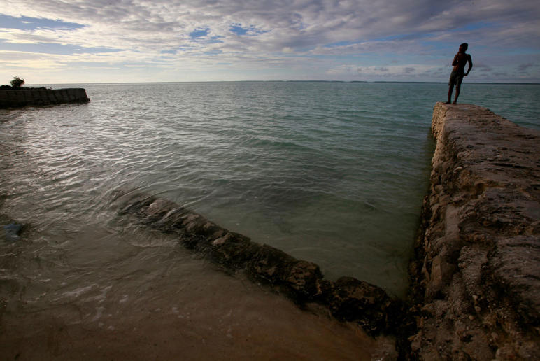 In this file photo, a boy stands on top of a seawall on South Tarawa in the central Pacific island nation of Kiribati.