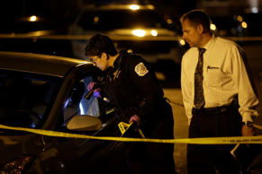 A Chicago Police officer and detective investigate a vehicle at the crime scene where a man was shot in the North Lawndale neighborhood on May 28, 2017 in Chicago, Illinois. The The Chicago Police Department added 1,300 extra officers around the city to patrol the streets for the Memorial holiday weekend.