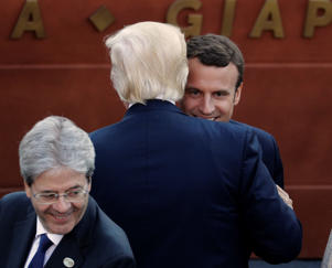 U.S. President Donald Trump embraces French President Emmanuel Macron as they arrive for a concert in the Ancient Theatre of Taormina in the Sicilian citadel of Taormina, Italy, on May 26, 2017.