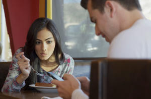 View of girlfriend eating and watching boyfriend use cell phone in restaurant