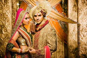 Portrait of bride and groom wearing traditional Indian clothing.