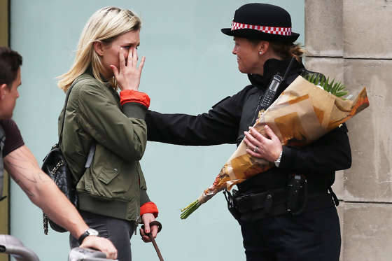 Slide 1 of 51: A woman reacts after asking a Police officer to lay flowers near London Bridge in London on June 4, as a tribute to the victims of the June 3 terror attack. Seven people were killed in a terror attack on Saturday by three assailants on London Bridge and in the bustling Borough Market nightlife district, the chief of London's police force said on Sunday.