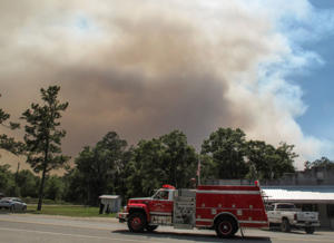 A fire truck passes as a plume of smoke rising from a wildfire burning, Monday, May 8, 2017, just outside the town of St. George, Ga.