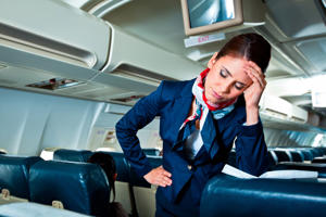 Young air stewardess suffering from headache on an airplane
