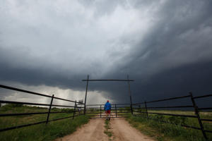 Center for Severe Weather Research intern Hunter Anderson takes photographs of a supercell thunderstorm, May 10, 2017 in Quanah, Texas.
