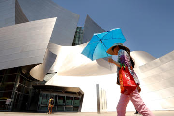 Stephanie Wong creates her own shade with an umbrella walking past Disney Hall baking in the sun of downtown Los Angeles on Monday June 20, 2016 as record-setting heat wave tightens its grip on the Southland.