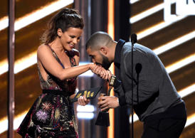 Drake kisses presenter Kate Beckinsale's hand as he walks on stage to accepts the award for top male artist at the Billboard Music Awards at the T-Mobile Arena on Sunday, May 21, 2017, in Las Vegas.