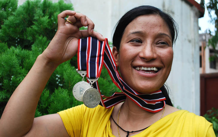 Indian mountaineer and mother of two children, Anshu Jamsenpa (32) holds her medals received from the Nepalese government for summiting Mount Everest twice, in Guwahati on June 3, 2011. Anshu Jamsenpa of Arunachal Pradesh summited Mount Everest twice in ten days - on May 12, 2011 and May 21, 2011.