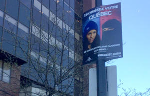 Police took down the sign depicting two women, one wearing a blue tuque and another wearing the Muslim niqab, but it has been re-installed.