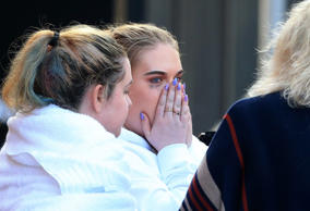 Young victims are visibly distressed as they leave a hotel that took-in victims ...