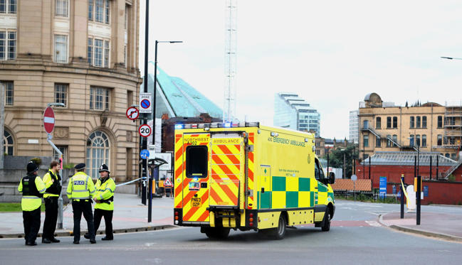Slide 2 of 27: An ambulance arrives as police officers stand at the Miller Street and Corporation Street Crossroads, near the Manchester Arena on May 23, 2017 in Manchester, England.