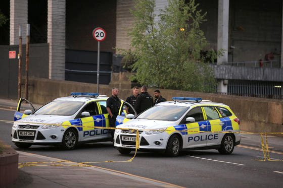 Slide 4 of 27: Police officers stand next to their vehicles near the Manchester Arena after a suspected terrorist attack at the end of a concert by US star Ariana Grande left 19 dead.