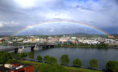 A rainbow pops out under dark rain clouds over the Willamette River in downtown Portland, Ore., on May 11, 2017.