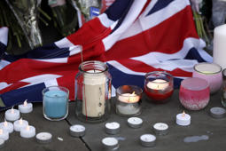 Flowers and candles are seen after a vigil in Albert Square, Manchester, England, Tuesday May 23, 2017, the day after the suicide attack at an Ariana Grande concert that left 22 people dead as it ended on Monday night.